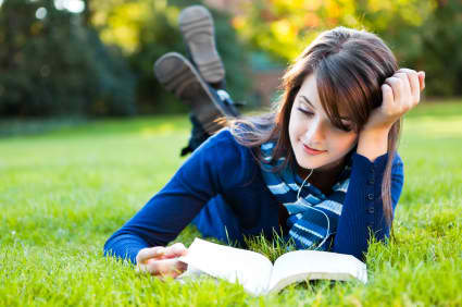 a girl reading book outdoor